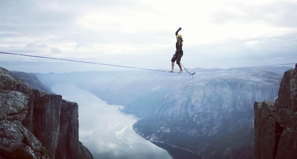 En person går barfota på lina mellan två bergformationer. Personen har säkerhetslina och hjälm.