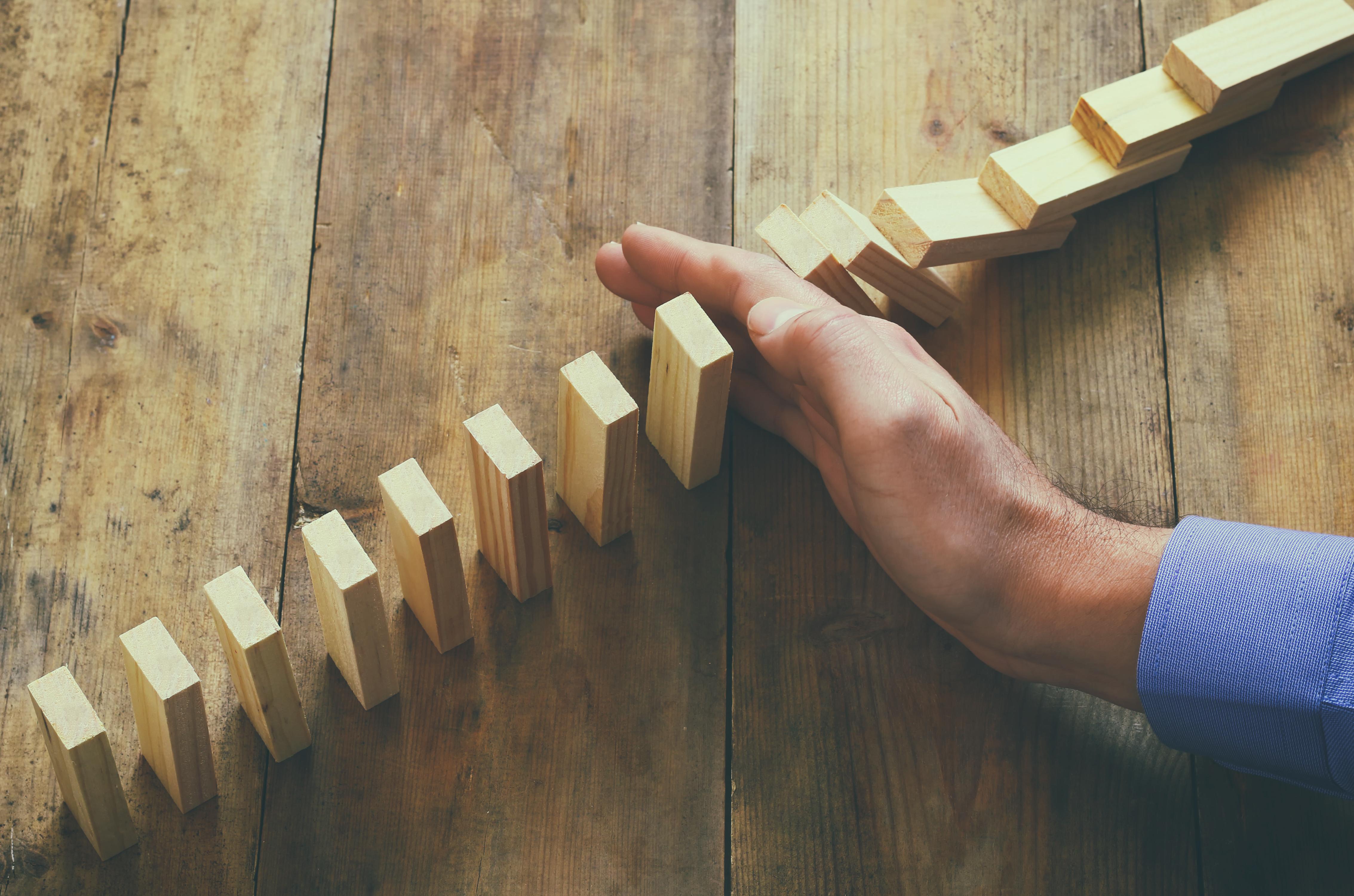 Hand stoppt Dominokette