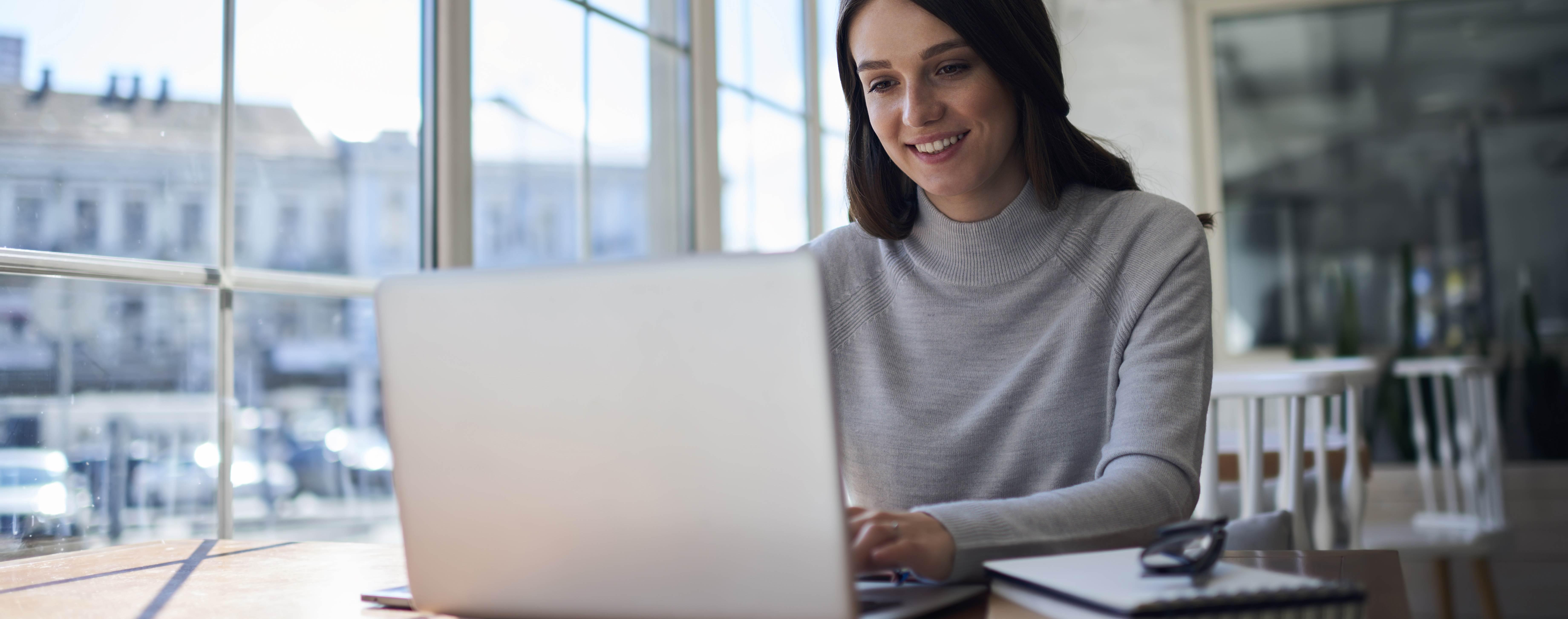 woman looking at webinar on laptop