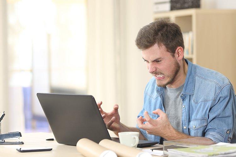 Mann sitzt veraergert vo seinem Laptop
