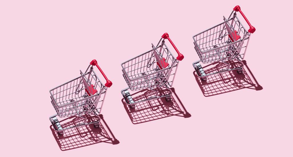 Three Shopping Carts over pink background