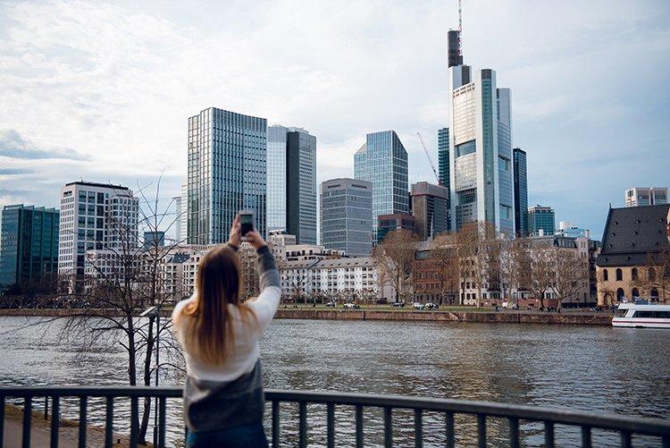 Frau fotografiert Skyline mit ihrem Handy