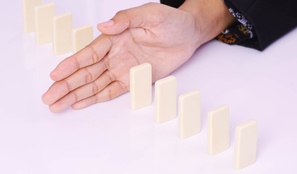 Business woman blocking domino in the middle - business, finance and compete concept