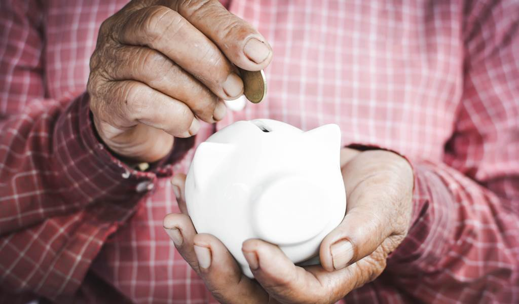 Old hands holding piggy bank and coins selective and soft focus vintage tone