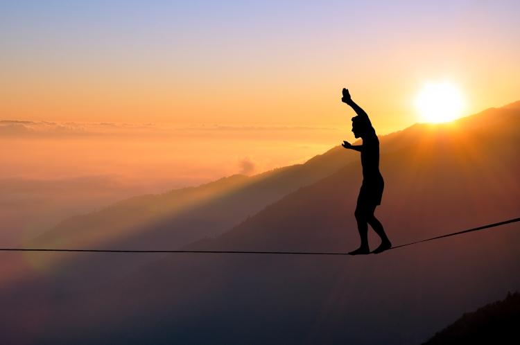 Mann balanciert über Seil vor Sonnenuntergang